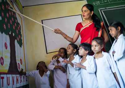 A teacher points to a chart on a wall, surrounded by her class of young children