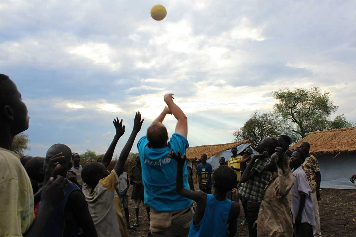 Aid worker playing with children in a village of South Sudan