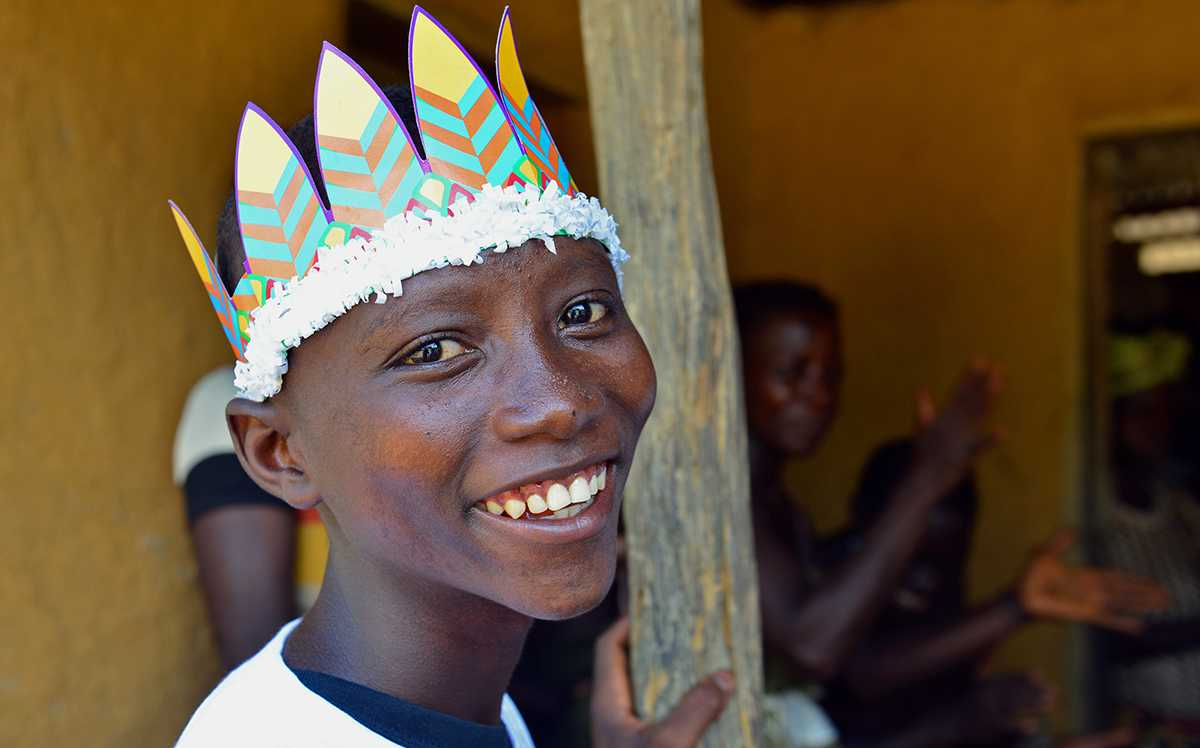 Young Ebola survivor smiling during community meeting