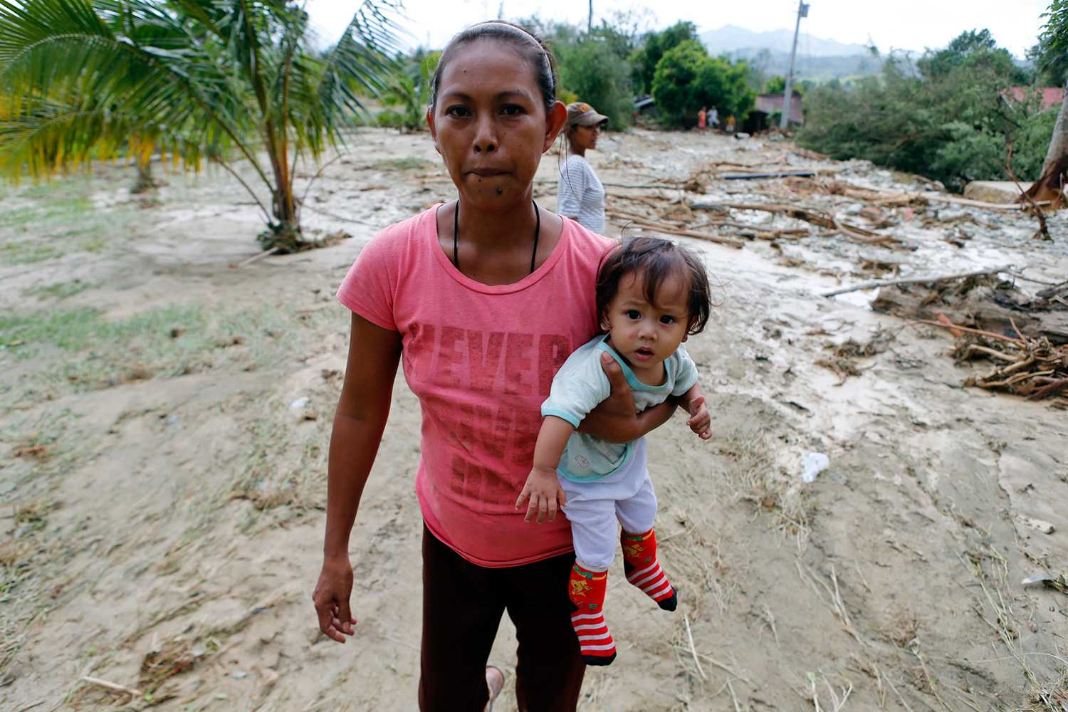 Mother carries daughter as they evacuate Laur after Typhoon Koppu