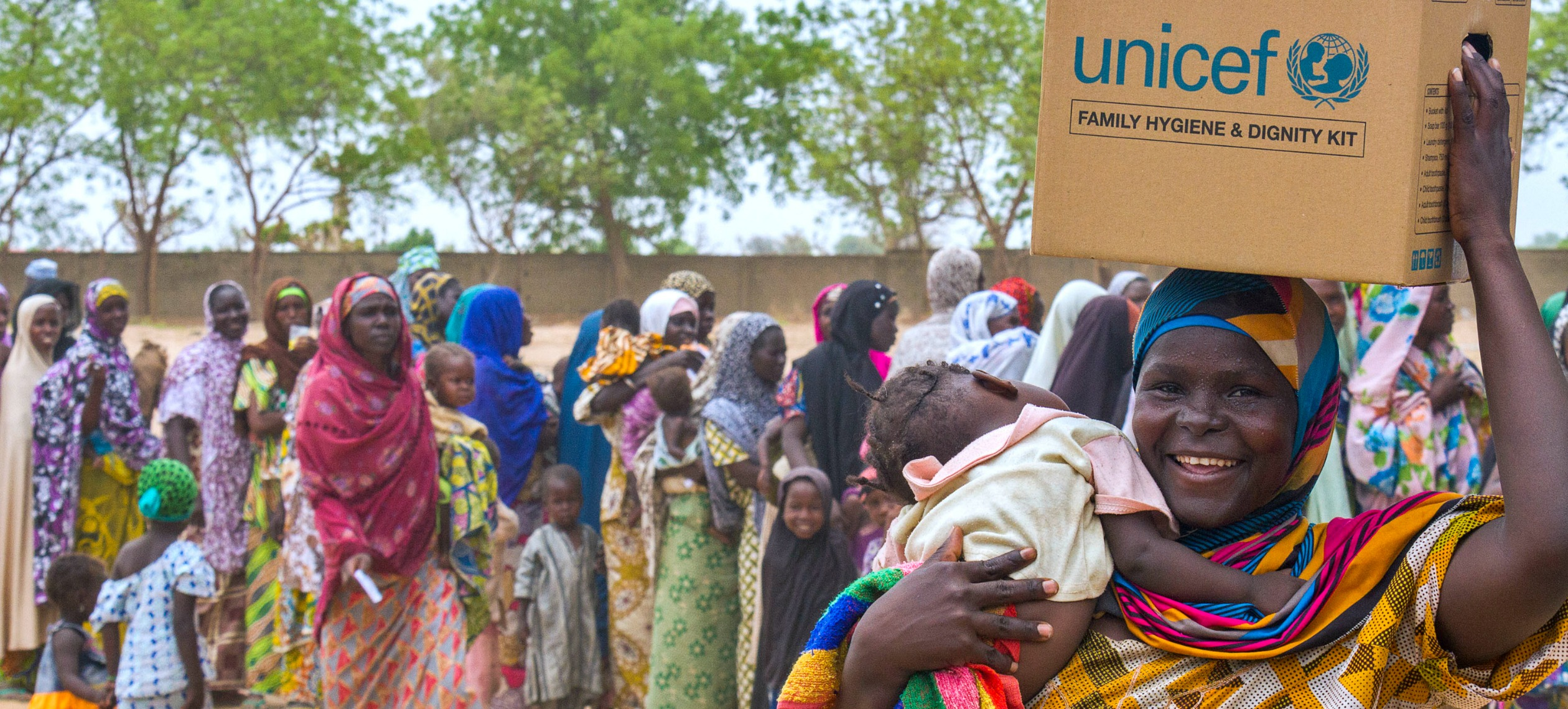 Women holding her baby and a UNICEF famly hygiene and dignity kit on her head