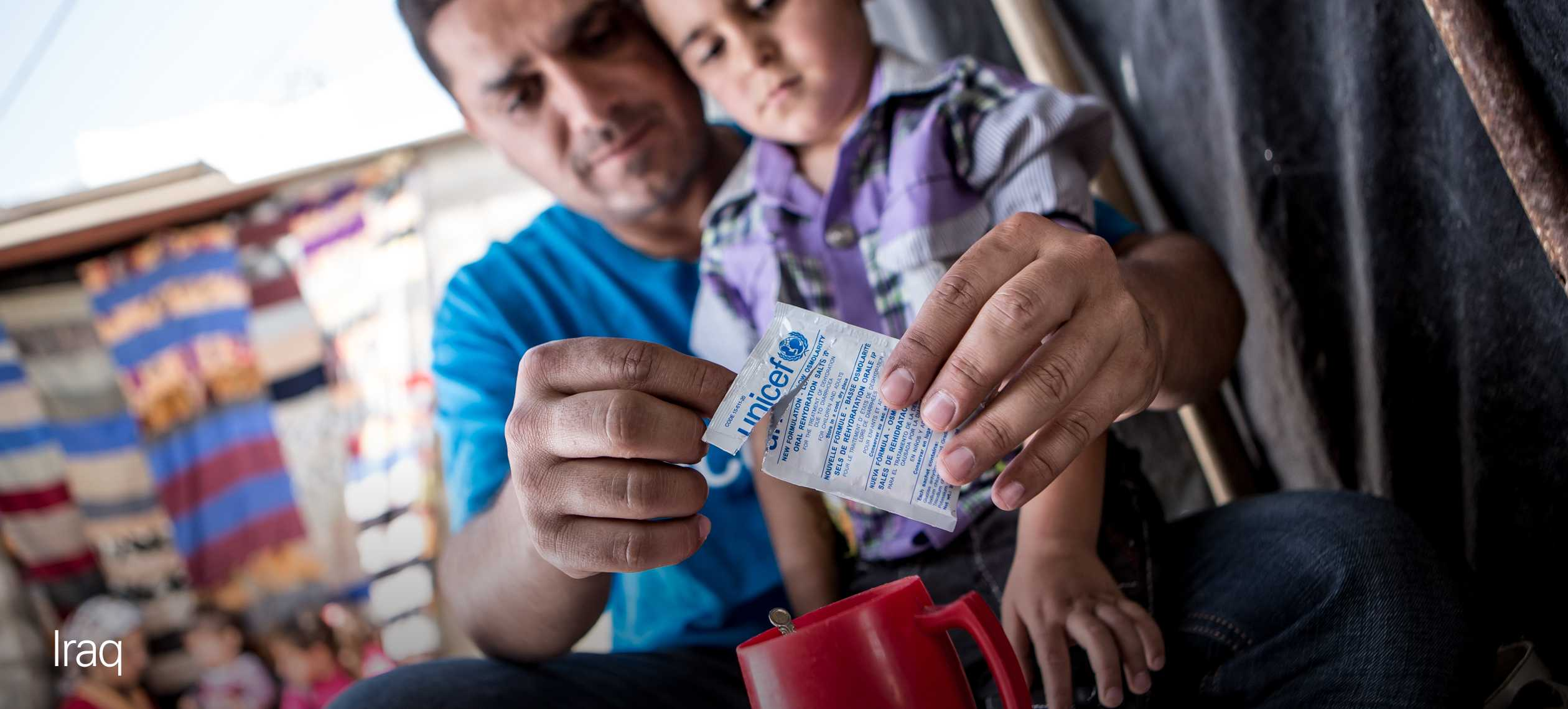 UNICEF Australia volunteer in Iraq giving a young boy oral rehydration salts