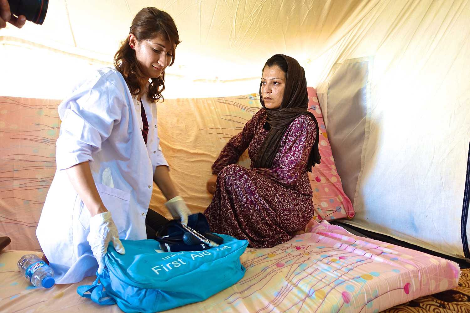 Volunteer nurse assisting a pregnant Syrian woman