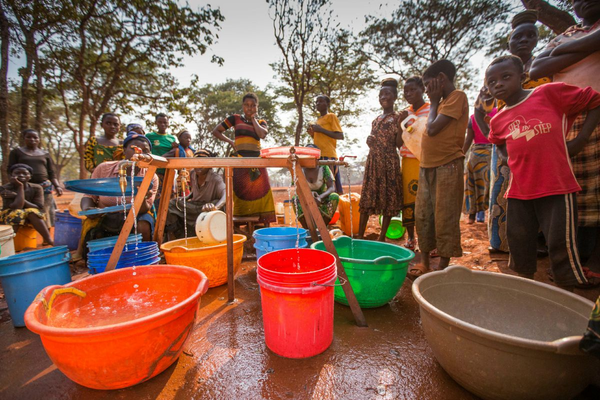 People gathered around a tap in a refugee camp in Tanzania